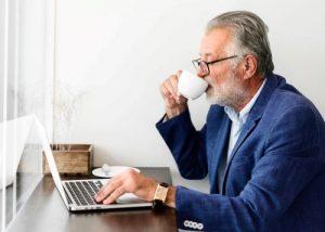 Gentleman at laptop reviewing his pension